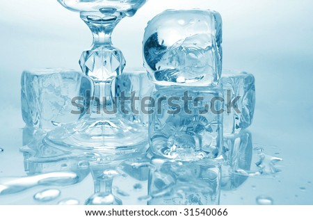 Melting ice cubes and glass with drink and ice, with reflection over monotone blue background