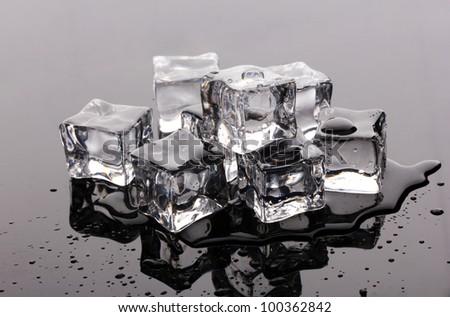 Melting ice cubes on grey background