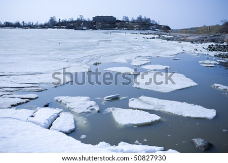 Melting ice in spring on the coast - stock photo