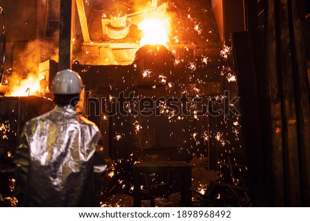 Melting iron in foundry and worker controlling the process iron casting and production. Metallurgy and heavy industry. Foto stock ©