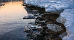 Melting river ice coast close up