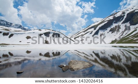 Melting snow and mountains slopes reflecting in a mountain lake in Italian Alps #1432026416