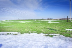 Melting snow on green grass close up - between winter and spring concept background
