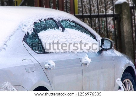 melting snow on the roof and windows of the car. Concept: thaw after snowfall, heavy snowfall. Soft focus #1256976505