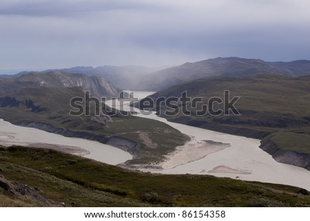 Melting water rivers from Russell Glacier, Kangerlussuaq, Greenland. Sand drifting is taking place above the river.