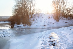Meltwater of tributary . Melting of snow . Sun shining in the winter . River with melting ice