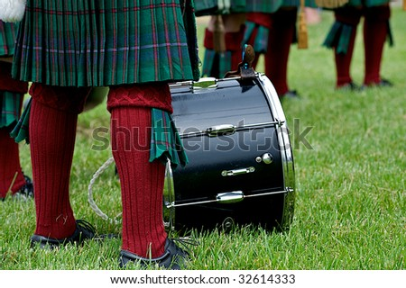 Members of a bagpipe band in Scottish kilts getting ready for a performance.