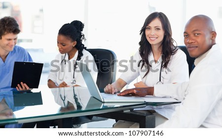 Members of a medical team looking at the camera while working on a laptop