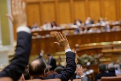 Members of Romanian Parliament vote by raising their hands