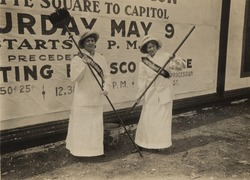 Members of the Congressional Union for Woman Suffrage holding brushes in front of billboard advertisement for the procession to Congress on May 9th, 1914 advocate National Woman Suffrage Amendment.
