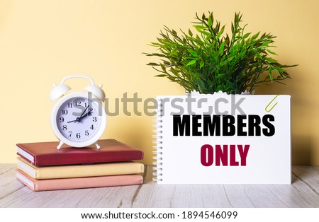 MEMBERS ONLY is written in a notebook next to a green plant and a white alarm clock, which stands on colorful diaries. Stock photo ©