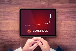 Meme stock investment warning concept with digital tablet. Soaring graph of stock or cryptocurrency and notification about meme stock hazardous investment, risk and threat.