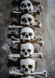 Memento more. Human Skeleton bones and skulls. Abstract concept Skeleton grave. Part of interior decorated marble skull and bones church wall hell.
