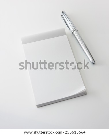 Memo pad and a silver pen, isolated on white with natural shadows. Intentionally highlighted on upper left hand corner. Focus is slightly below memopad top (where messages are likely inserted.)