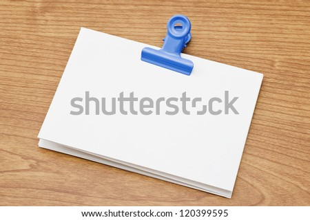 Memo pad and paper clip on wooden desk