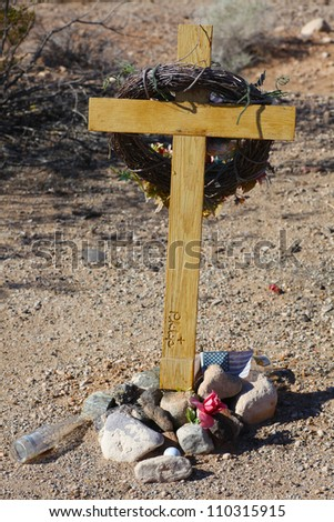 Memorial along Route 66/Wooden cross set along US 66 with crown of thorns hanging from top & empty beer bottle at the base.