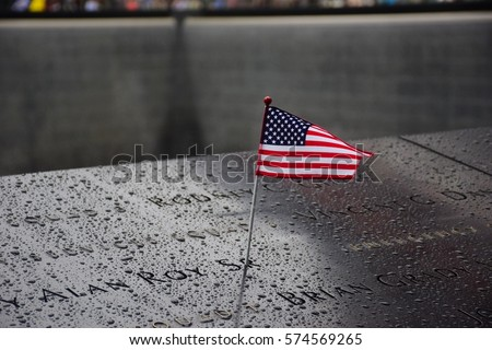 Shutterstock Memorial at Ground Zero Manhattan for September 11 Terrorist Attack with an American Flag Standing near the Names of Victims Engraved