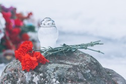 Memorial flowers. Carnations in commemoration of the war. Victory Day, memorial flowers on a stone and a candlestick.
