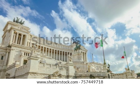 memorial monument the Vittoriano or Altar of the Fatherland, in Venezia square, with waving italian flag. Italian and Rome patriotic symbols, located on the Campidoglio hill in Rome #757449718