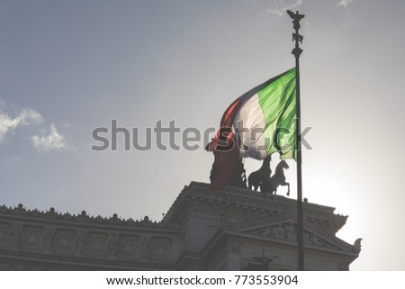 Memorial monument the Vittoriano or Altar of the Fatherland, in Venezia square, with waving italian flag. Italian and Rome patriotic symbols, located on the Campidoglio hill in Rome. #773553904