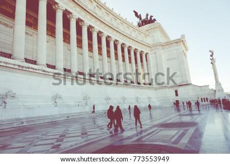 Memorial monument the Vittoriano or Altar of the Fatherland, in Venezia square, with waving italian flag. Italian and Rome patriotic symbols, located on the Campidoglio hill in Rome. #773553949