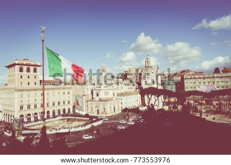 Memorial monument the Vittoriano or Altar of the Fatherland, in Venezia square, with waving italian flag. Italian and Rome patriotic symbols, located on the Campidoglio hill in Rome. #773553976