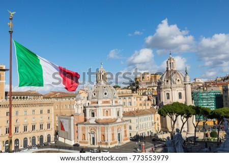 Memorial monument the Vittoriano or Altar of the Fatherland, in Venezia square, with waving italian flag. Italian and Rome patriotic symbols, located on the Campidoglio hill in Rome. #773553979
