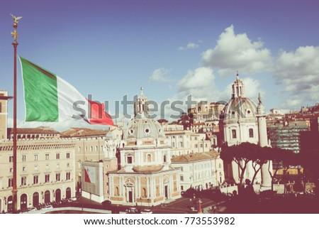 Memorial monument the Vittoriano or Altar of the Fatherland, in Venezia square, with waving italian flag. Italian and Rome patriotic symbols, located on the Campidoglio hill in Rome. #773553982