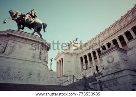 Memorial monument the Vittoriano or Altar of the Fatherland, in Venezia square, with waving italian flag. Italian and Rome patriotic symbols, located on the Campidoglio hill in Rome. #773553985