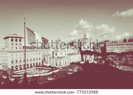 Memorial monument the Vittoriano or Altar of the Fatherland, in Venezia square, with waving italian flag. Italian and Rome patriotic symbols, located on the Campidoglio hill in Rome. #773553988