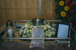 Memorial service before burial with visible picture frame, metal urn with ashes and bouquet. Sad grieving moment.