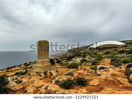 Memorial to General Sir Walter Norris Congreve and Hagar Qim megalithic temple complex on the Mediterranean island of Malta with blue mediterranean sea in a background in spring cloudy day #1229921521