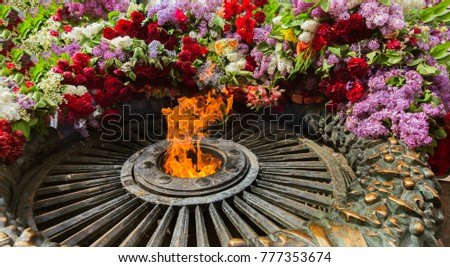 """Memorial to memory of Unknown Sailor of Eternal Flame to fallen defenders of Fatherland with flowers around fire. """"Eternal Flame"""" in memorial to fallen defenders of homeland. Victory Day, ODESSA, 2016 #777353674"""