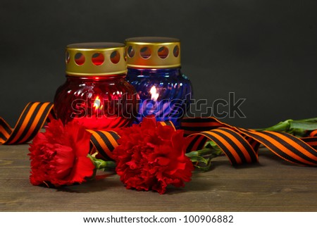 Memory lantern with candles, red carnations and St. George ribbon on wooden table on grey background