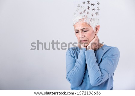 Memory loss due to dementia. Senior woman losing parts of head as symbol of decreased mind function. Senior woman losing parts of head feeling confused as symbol of decreased mind function.