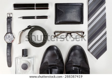 Men accessories. Black elegant accessories pieces isolated on white wooden table. Top view.