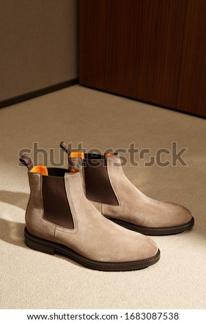 Men accessories. Custom made men's classic beige suede chelsey shoes in minimalist luxury tailor studio apartment. Handcrafting, small business workshop concept. Closeup with copy space shopwindow ima Stock fotó ©