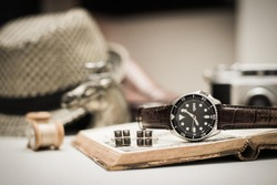 Men accessories on wooden desk. Closeup at luxury men watch with black dial and leather strap.