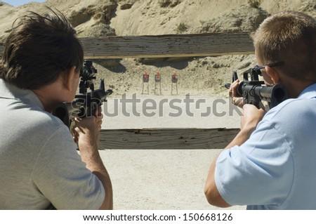 Men aiming rifles at firing range