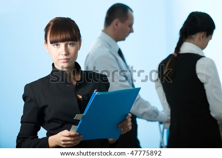 Men and women and girl with blue folder