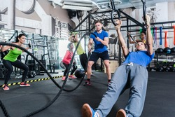 Men and women at functional fitness training in gym doing sport on rings and rope