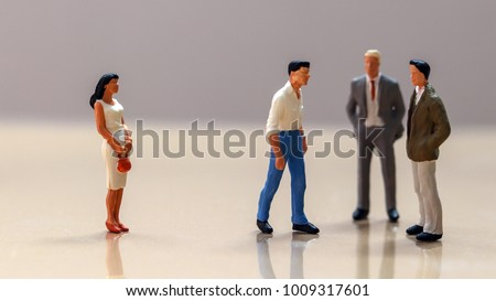 Men and women at work. Miniaturewomanand agroupofminiaturemen.