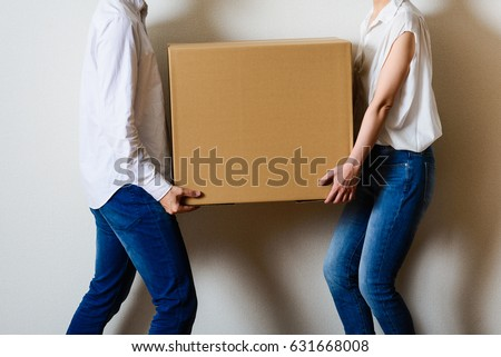 Men and women couple carrying a cardboard box
