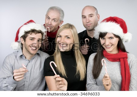 Men and women in Santa hats holding candy canes - stock photo