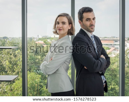 Men and women in the airs, business people standing, arms crossed, looking back and looking at the camera. The dress looks good and is reliable. With a transparent glass backdrop Can see the scenery #1576278523