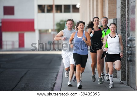 Men and women running for exercise downtown