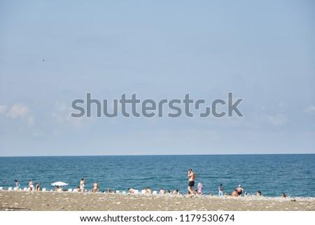 men and women sunbathe and bathe on the beach of Batumi in the afternoon. Georgia. #1179530674