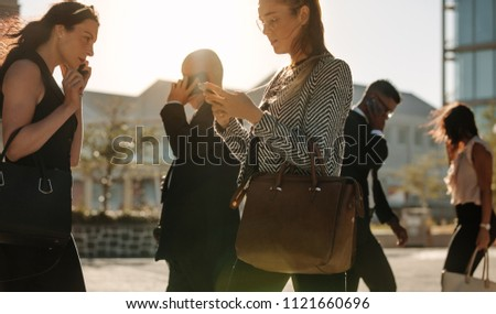 Men and women using mobile phone while commuting to office on a crowded street with sun flare in the background.