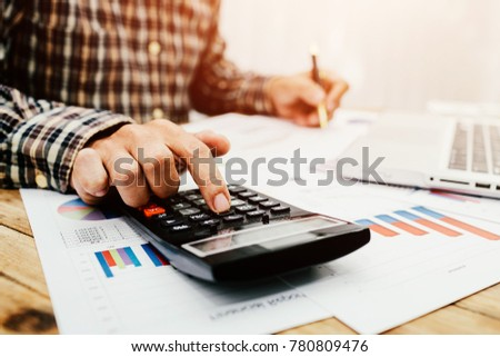 Men are calculating individual income tax to send information to government agencies. Using a laptop and a calculator.
