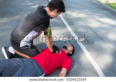 Men are doing first aid by Cardiopulmonary Resuscitation or CPR to friends with sudden cardiac arrest. During exercise together Within the park #1024613569